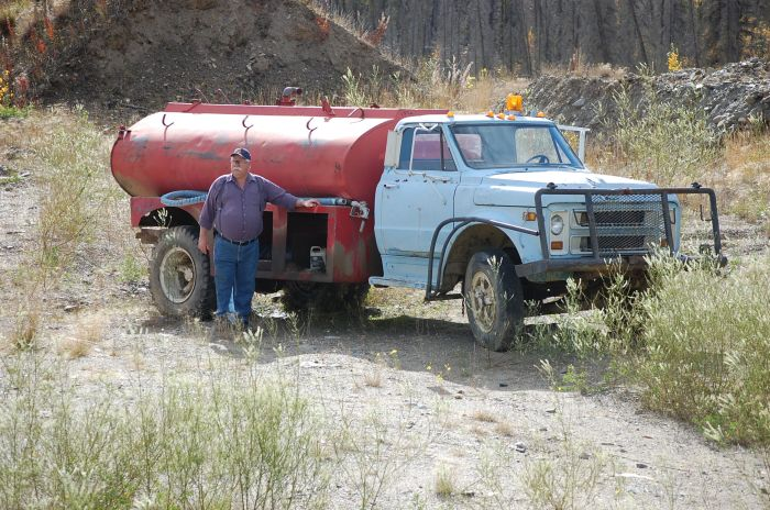 Deputy Chief Taylor, our Museum Curator, stands by the truck to which the tank is now attached, on an old mining claim